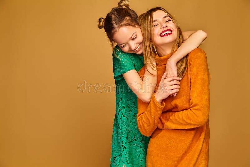2 красивых белокурых девушки представляя на золотой предпосылке стоковые фото