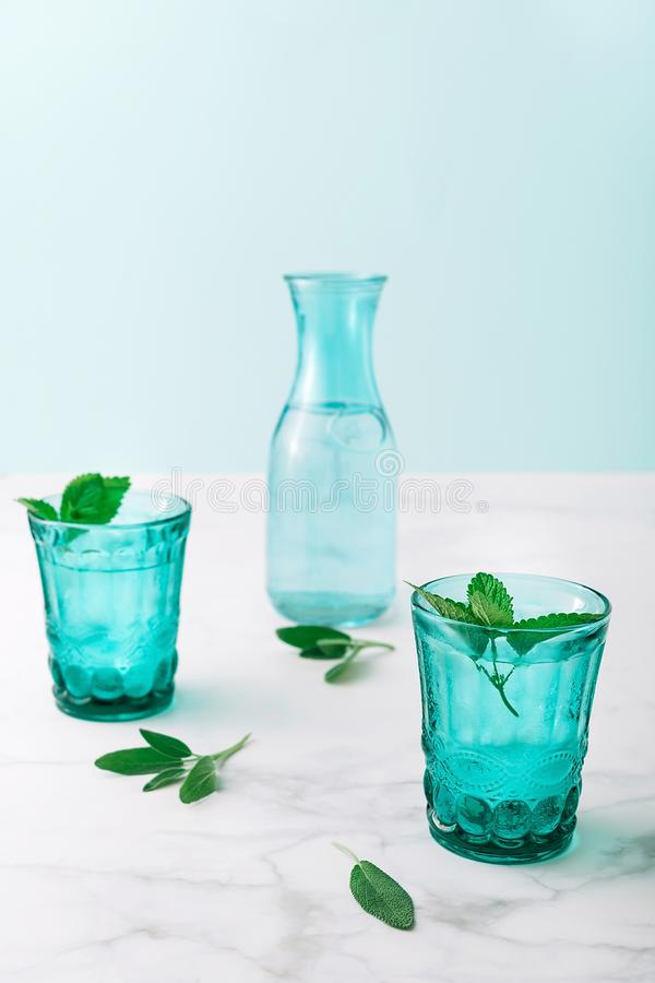2 красивых винтажных стекла бирюзы и бутылка с кубами холодного напитка и льда, украсили со свежей зеленой мятой стоковое фото rf