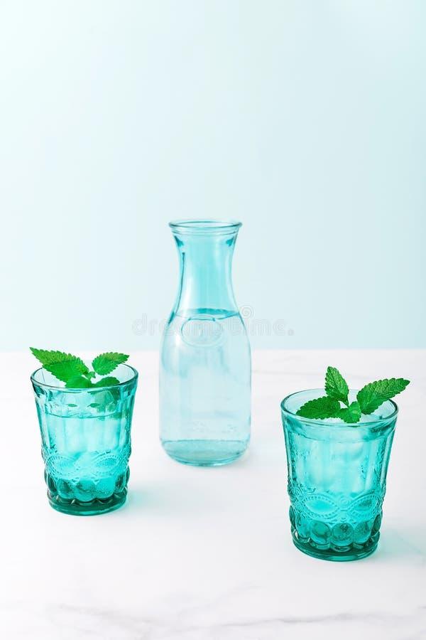 2 красивых винтажных стекла бирюзы и бутылка с кубами холодного напитка и льда, украсили со свежей зеленой мятой стоковое изображение