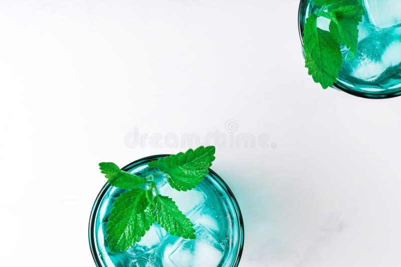 2 красивых винтажных стекла бирюзы с кубами холодного напитка и льда, украсили со свежей зеленой мятой выходят на белое стоковое изображение rf