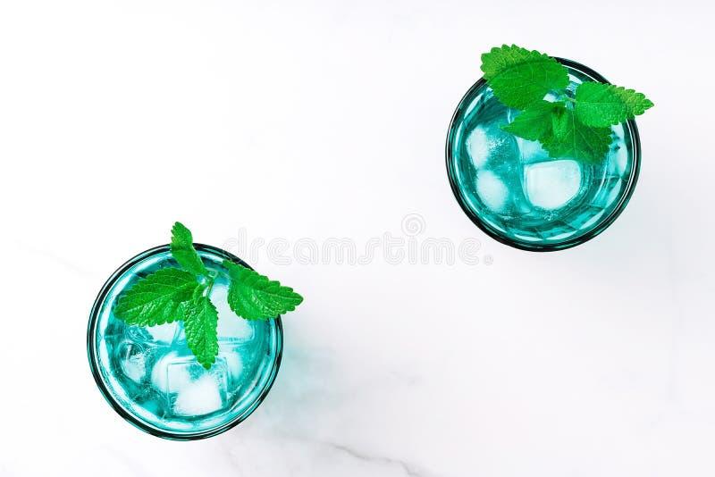 2 красивых винтажных стекла бирюзы с кубами холодного напитка и льда, украсили со свежей зеленой мятой выходят на белое стоковое изображение