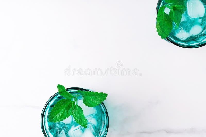 2 красивых винтажных стекла бирюзы с кубами холодного напитка и льда, украсили со свежей зеленой мятой выходят на белое стоковые изображения rf