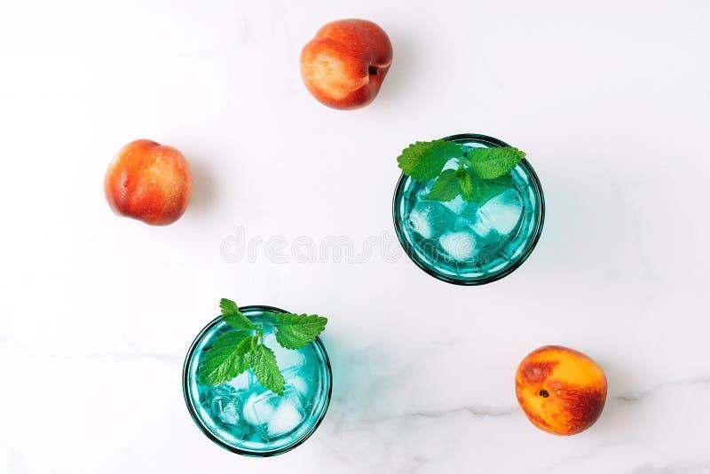 2 красивых винтажных стекла бирюзы с кубами холодного напитка и льда, украсили со свежими зелеными листьями и 3 мяты стоковые изображения rf