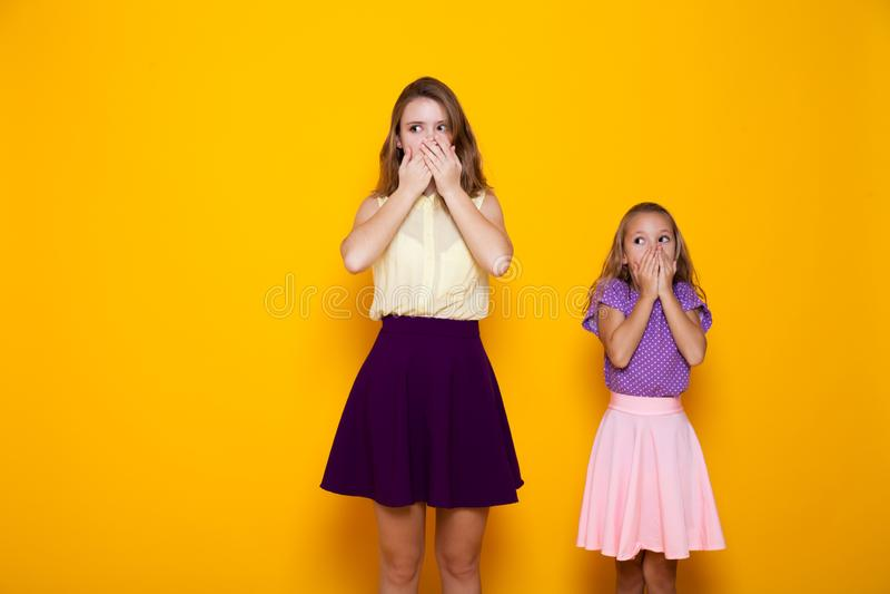 2 красивых девушки закрывают безмолвие и тайну рта стоковые изображения