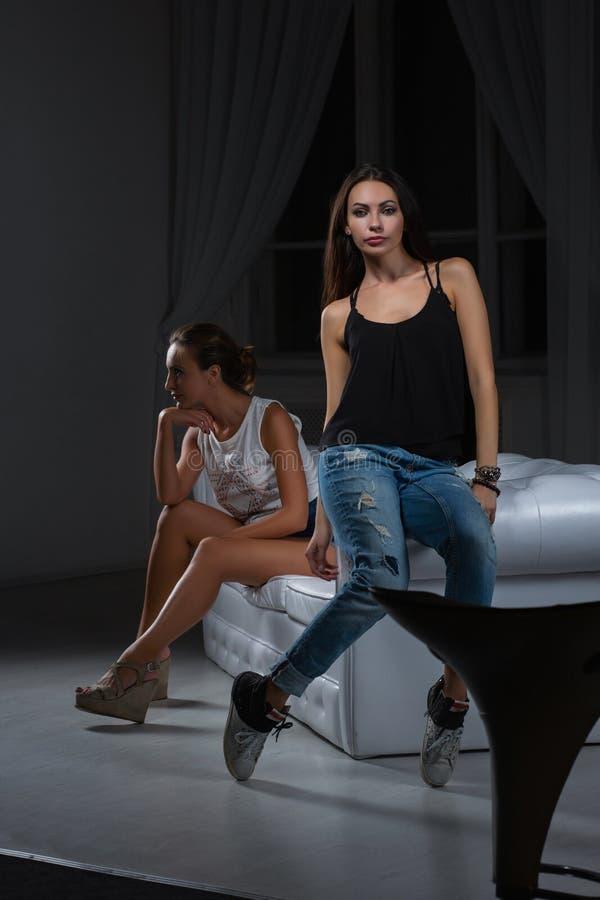 2 красивых девушки представляя в студии стоковые изображения rf