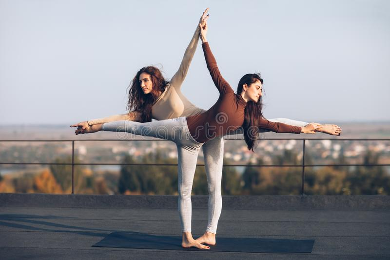 2 красивых женщины делая virabhadrasana asana йоги на крыше стоковое фото