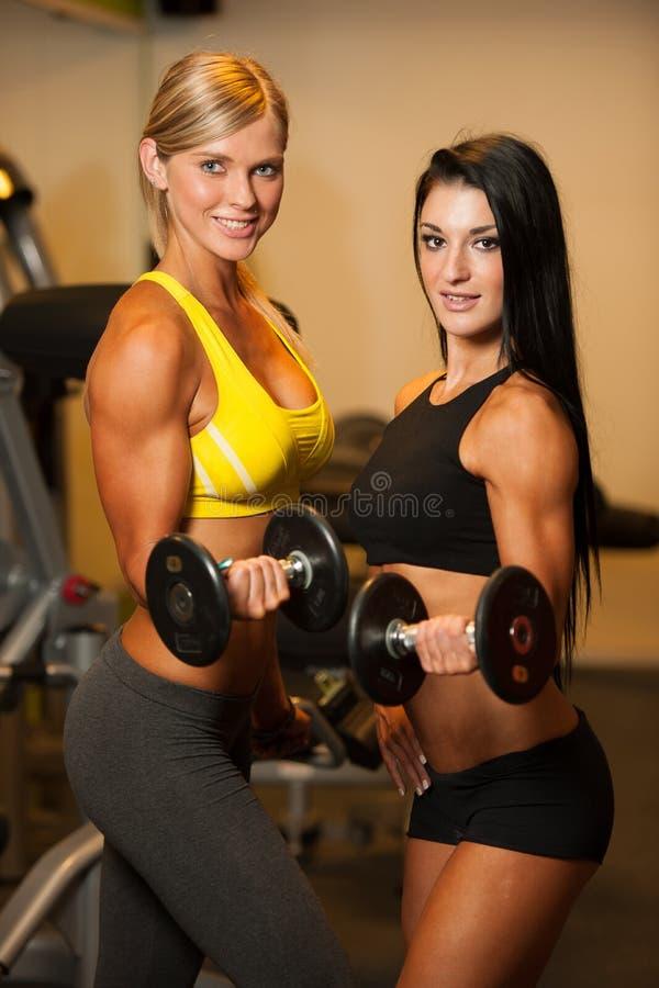 2 красивых женщины разрабатывая с гантелями в фитнесе стоковое фото