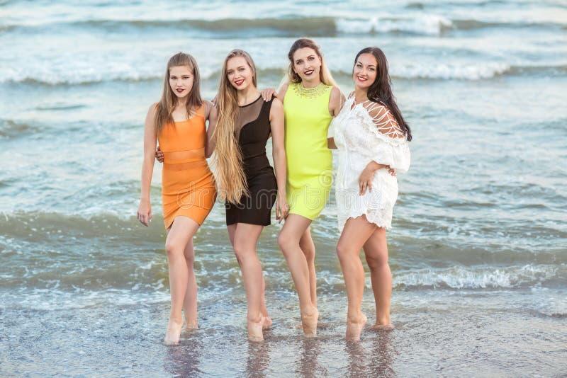 4 красивых маленькой девочки стоят на заднем плане берега моря, полно-длин Очаровательные молодые женщины в пестротканом стоковые фотографии rf