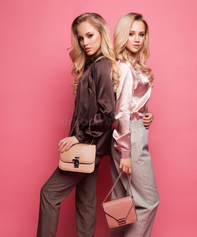 2 красивых молодой женщины в случайных одеждах представляя над розовой предпосылкой стоковые изображения