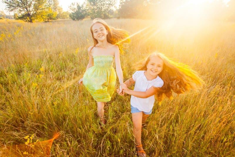 2 красивых сестры бежать на лужайке в природном парке внешнем в летнем времени Свобода и беспечальное стоковая фотография