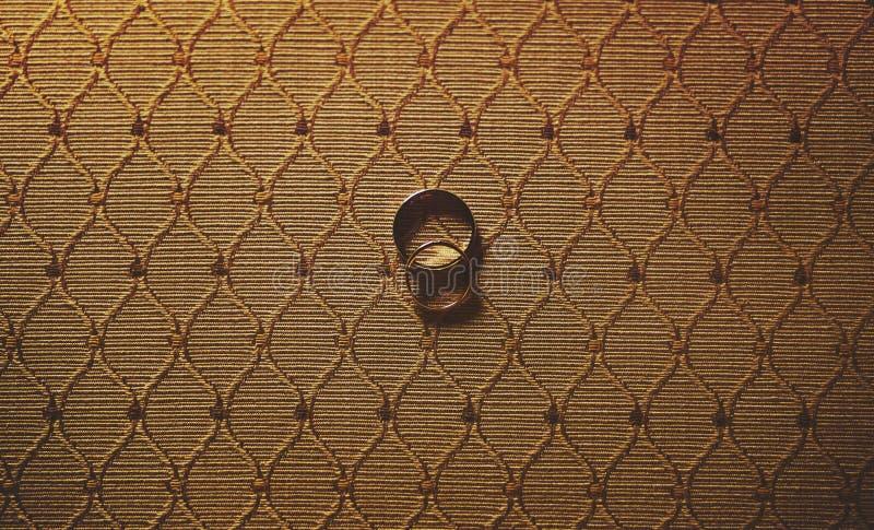 2 красивых элегантных обручального кольца серебр и золото на bac ткани стоковая фотография rf