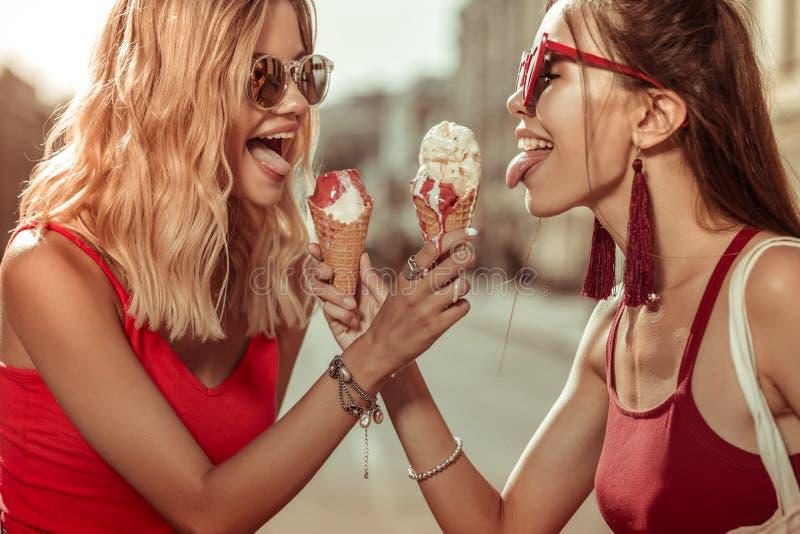 2 красивых alluring красоты молод-взрослого эмоциональных держа мороженое в руках стоковые изображения rf