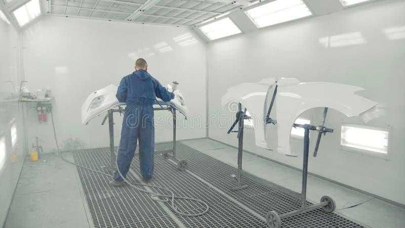 Краска автоматического художника распыляя белая на бампере автомобиля переднем в специальной будочке стоковое фото
