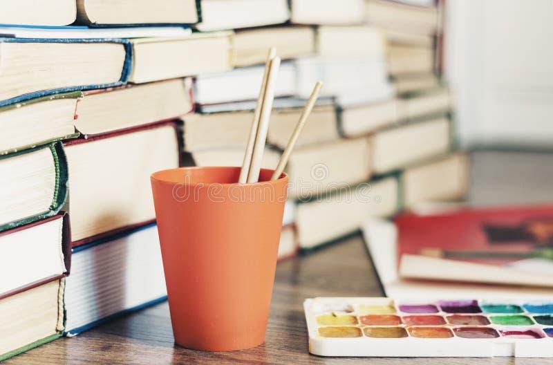 Краска акварели, щетки хорошо использовала и лист бумаги на деревянном столе со стогом предпосылки книг стоковое изображение rf