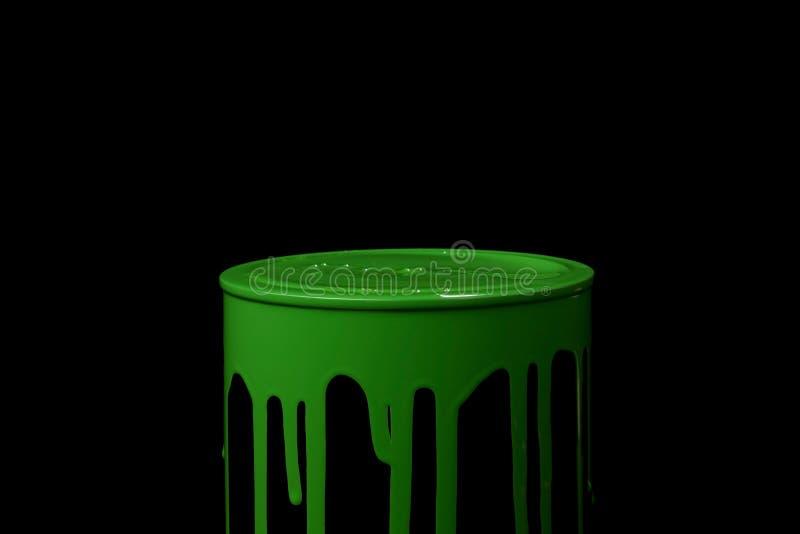 Краска зеленого масла пропуская вниз на стене ведра металла Изолировано над черной предпосылкой стоковая фотография rf