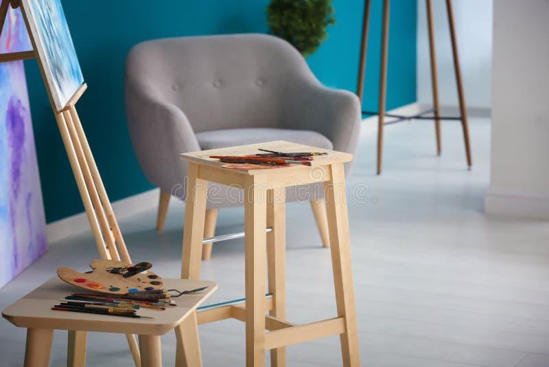 Краски и инструменты на стульях в мастерской художника стоковое фото