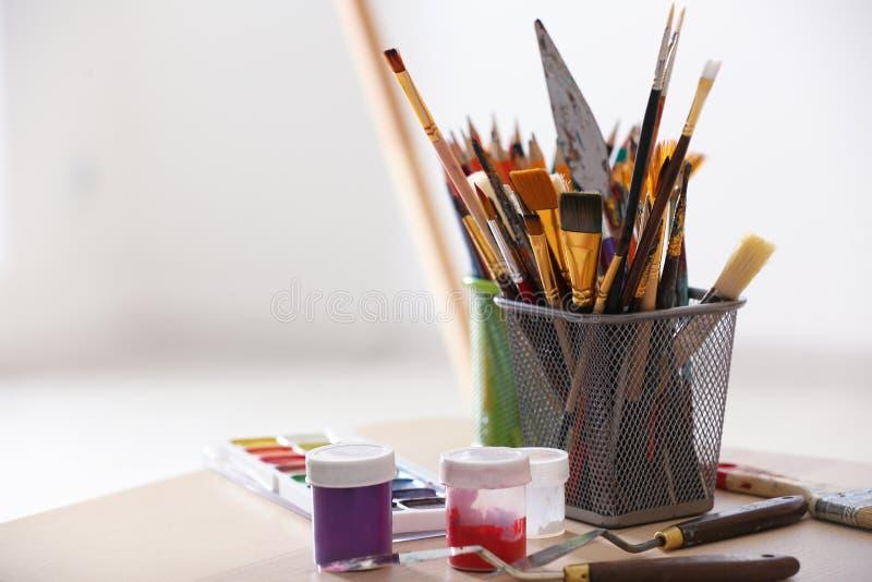 Краски и инструменты художника на таблице стоковая фотография rf