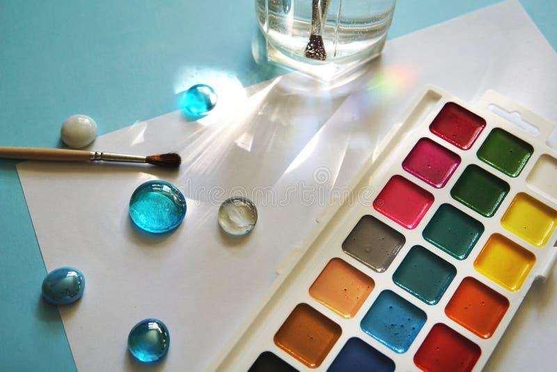 Краски и лист бумаги на голубой предпосылке стоковая фотография rf