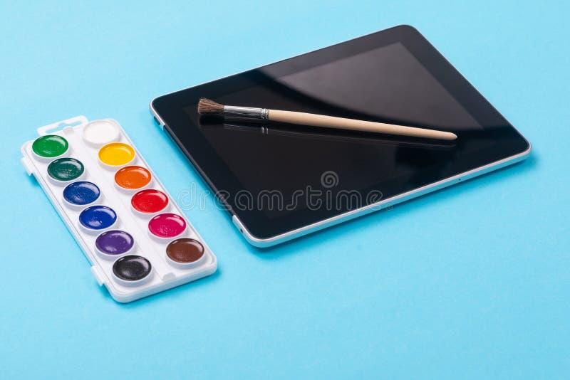 Краски и щетка акварели лежа на планшете изолированном на голубой предпосылке стоковые фотографии rf