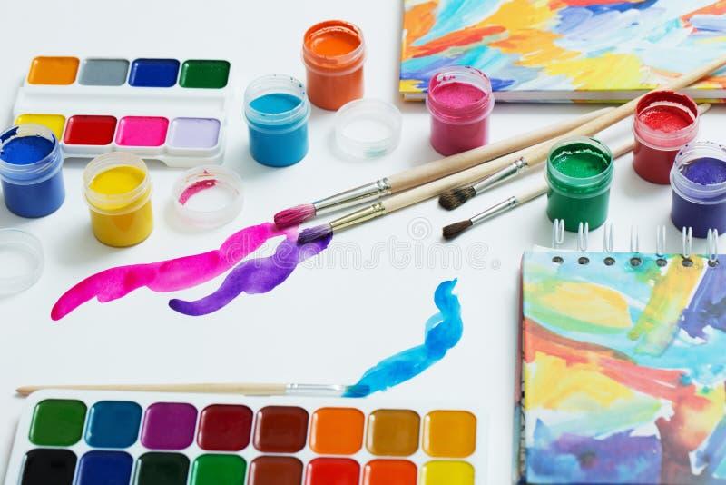 Краски и щетки на бумаге стоковые фото