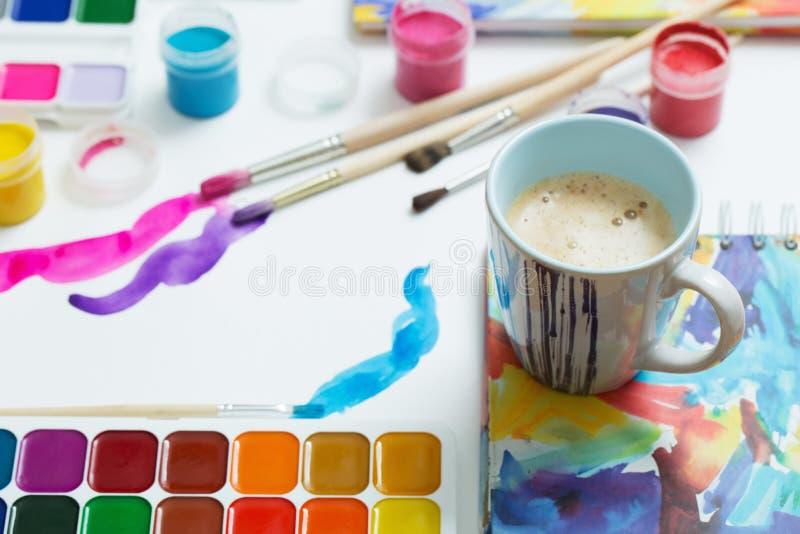 Краски, щетки и чашка кофе на бумаге стоковые изображения