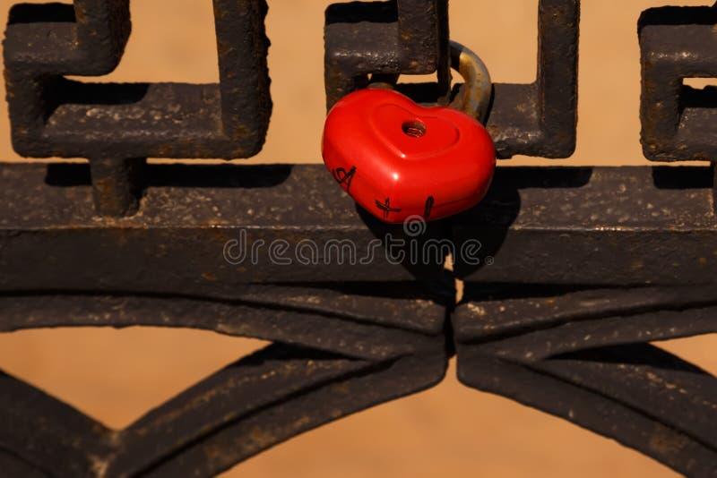 Красная в форме сердц смертная казнь через повешение замка на загородке металла стоковые фотографии rf