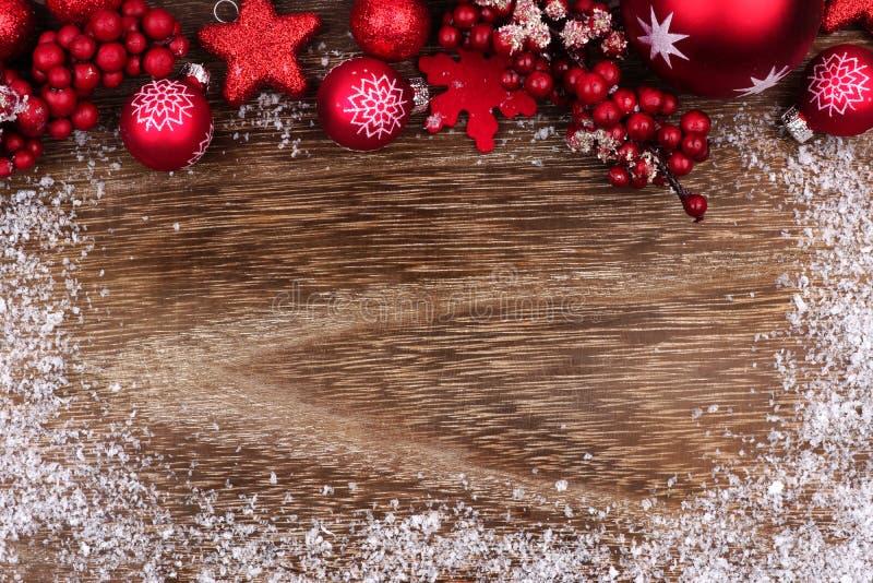 Красная граница верхней части орнамента рождества с рамкой снега на древесине стоковая фотография