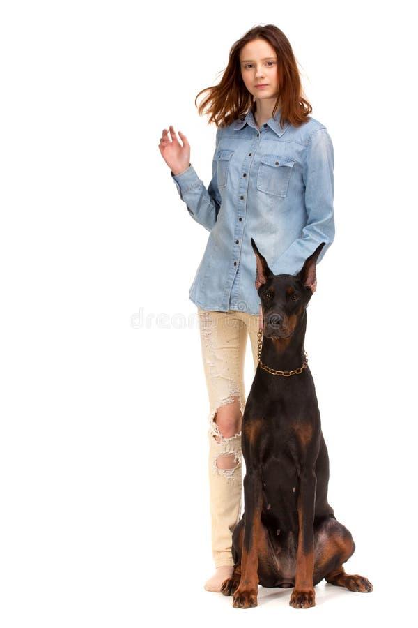 Красная девушка в джинсах с большой собакой стоковое изображение rf