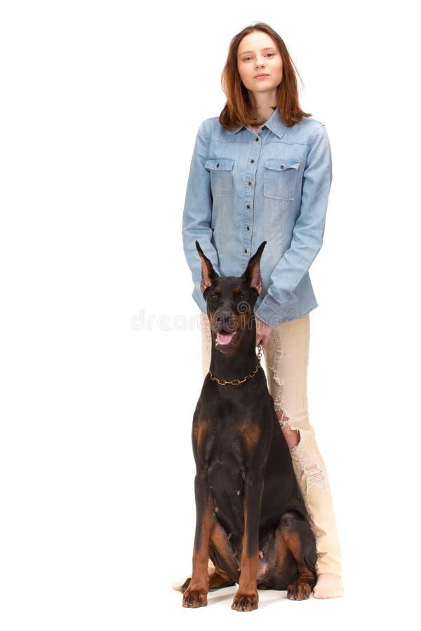 Красная девушка в джинсах с большой собакой стоковая фотография
