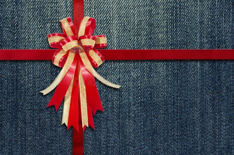 Красная лента на детальной развертке джинсов для предпосылки стоковое изображение