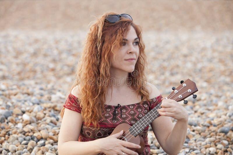 Красная женщина волос играя гавайскую гитару стоковая фотография rf