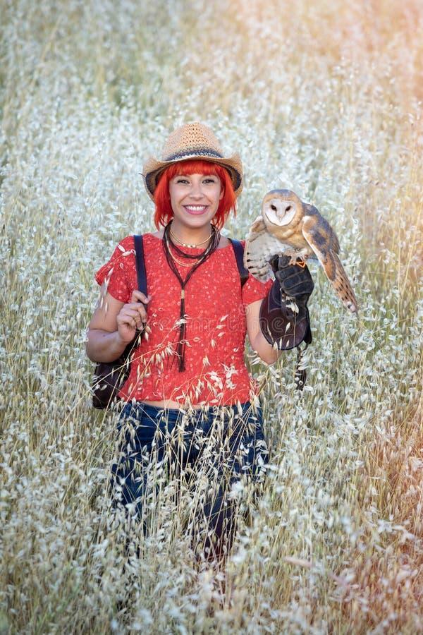 Красная женщина волос с белым сычом на ее руке стоковые фото