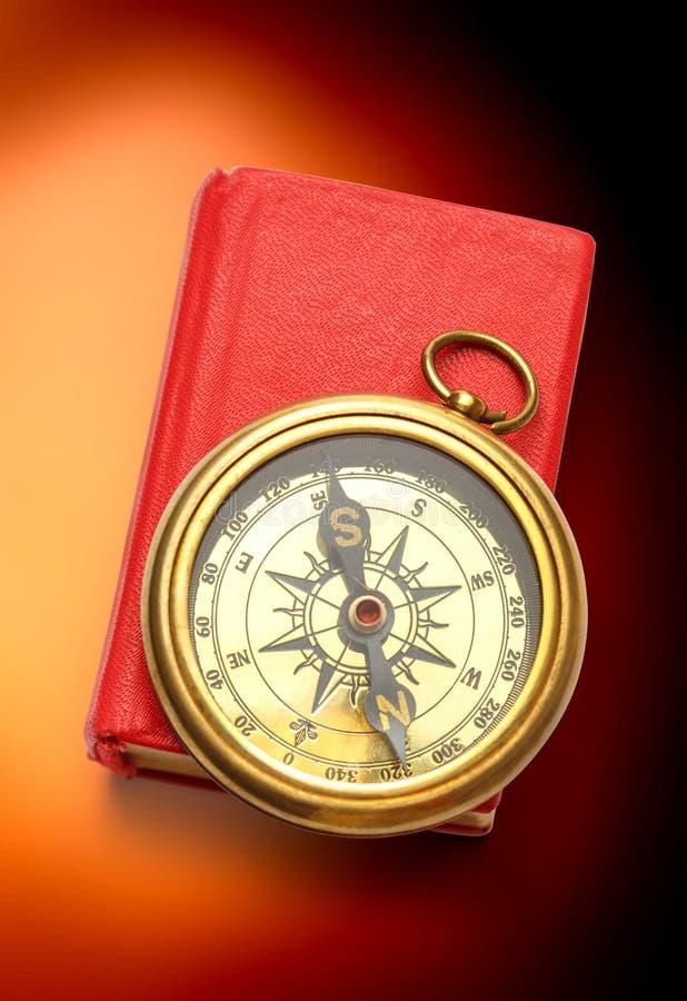 Красная закрытая книга с ретро компасом стоковые фото