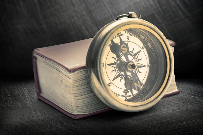 Красная закрытая книга с ретро компасом стоковые фотографии rf