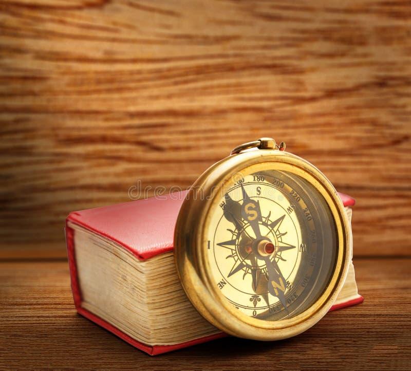 Красная закрытая книга с ретро компасом стоковые изображения