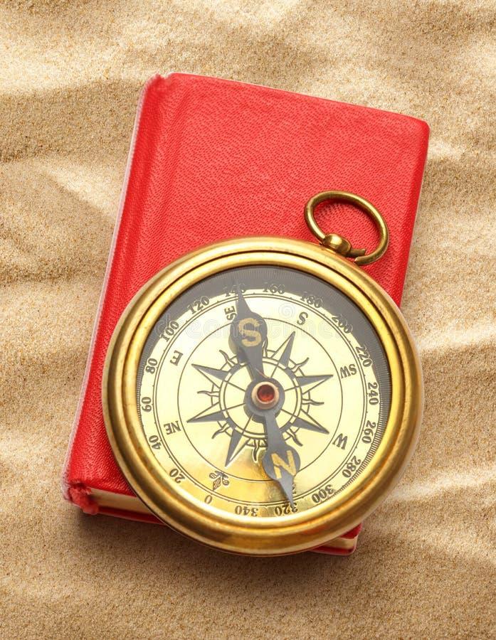 Красная закрытая книга с ретро компасом стоковое фото rf