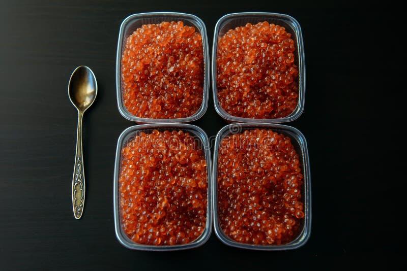 Красная икра в пластмасовых контейнерах близко вверх, взгляд сверху, черная предпосылка Изысканная еда стоковые фото