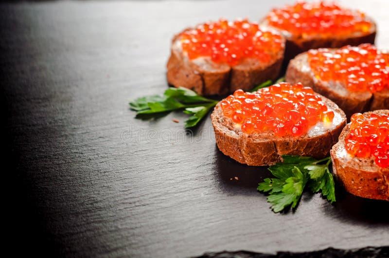 Красная икра на черном хлебе с маслом еда здоровая Закуска рыб Темная предпосылка стоковые фотографии rf