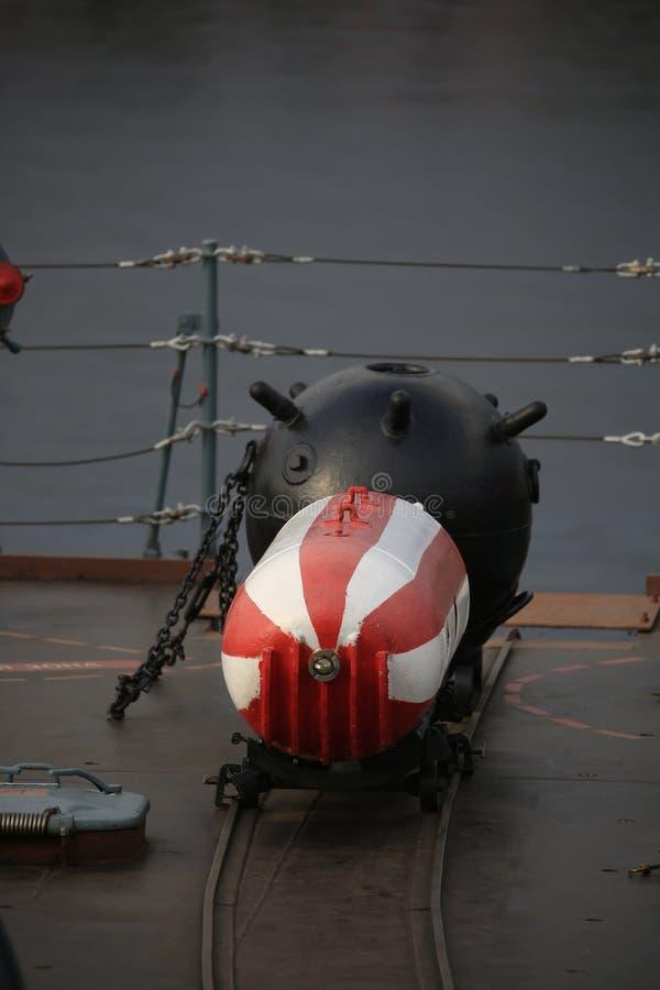Красная и белая внеконтактная шахта и черная контактная мина около рельса предохранителя на кормке военного корабля стоковое фото rf