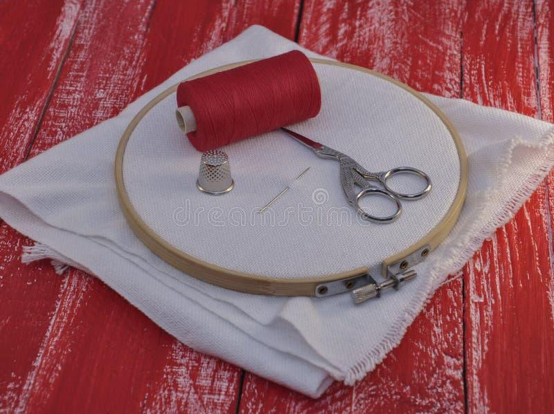 Красная катышка потока и ткани в деревянном обруче вышивки стоковая фотография rf