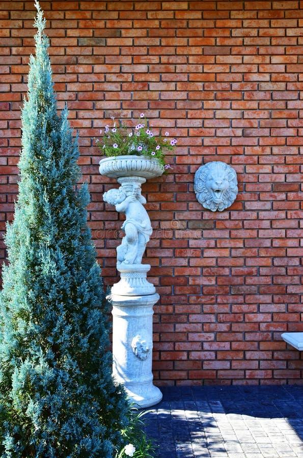 Красная кирпичная стена со скульптурой стороны льва стоковое фото