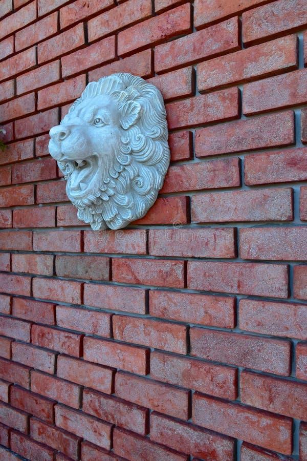 Красная кирпичная стена со скульптурой стороны льва стоковая фотография rf