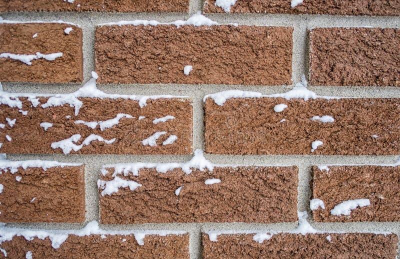 Красная кирпичная стена с снегом стоковые изображения