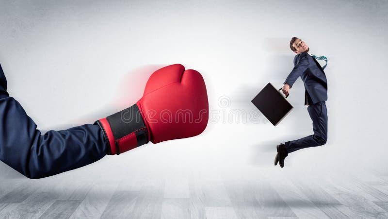 Красная кладя в коробку перчатка стучает вне меньшим бизнесменом стоковая фотография