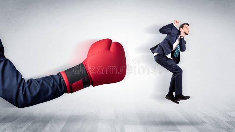 Красная кладя в коробку перчатка стучает вне меньшим бизнесменом стоковое изображение rf