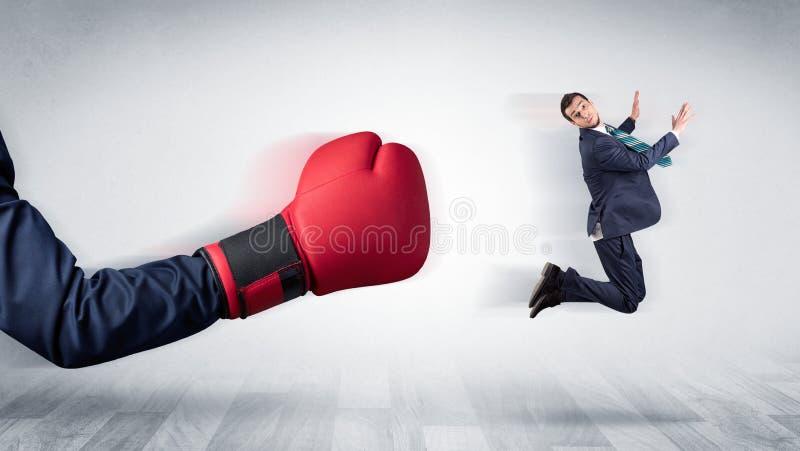 Красная кладя в коробку перчатка стучает вне меньшим бизнесменом стоковое фото