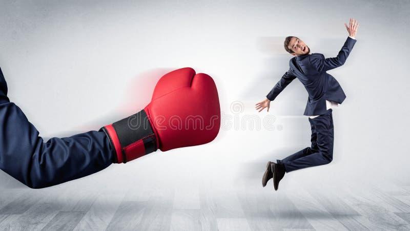 Красная кладя в коробку перчатка стучает вне меньшим бизнесменом стоковое изображение