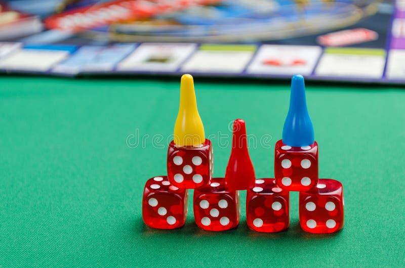 Красная кость для настольных игр с обломоками на зеленой предпосылке стоковые фотографии rf