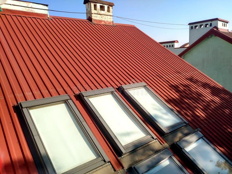 Красная крыть черепицей черепицей крыша дома с окнами чердака Настилать крышу конструкция, установка окна, современная концепция  стоковые изображения
