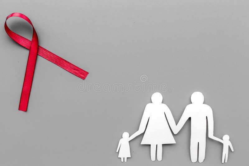 Красная лента для ВИЧ, СПИД, токсикомания и осведомленность анорексии около бумажного силуэта семьи на серой предпосылке покрываю стоковые изображения rf